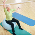 35084417 - senior woman sitting on a pilates ball and lifting dumbbells looking at camera. old caucasian woman exercising with weights at gym.